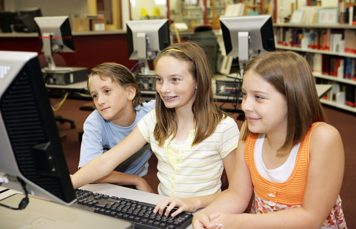 A group of school children having fun working on a computer in the school media center.